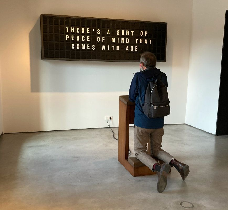 man kneeling in an art installation in front a mechanical display